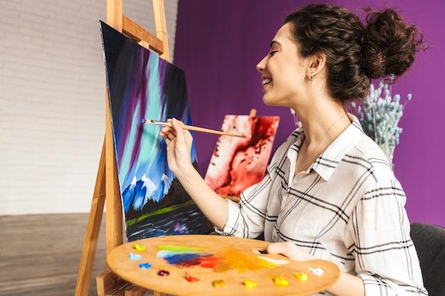 Bella donna artistica creativa che dipinge a casa, tenendo la tavolozza