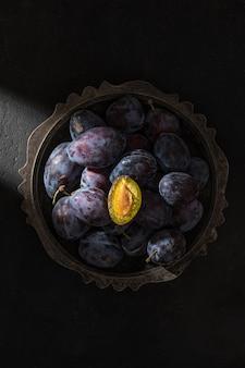 Colpo artistico creativo di prugne blu mature fresche in una ciotola nel raggio di luce con metà della frutta su sfondo nero. vista dall'alto