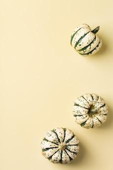 Composizione creativa del giorno del ringraziamento autunnale autunnale con zucche decorative. lay piatto, vista dall'alto, copia spazio, sfondo giallo natura morta per biglietto di auguri