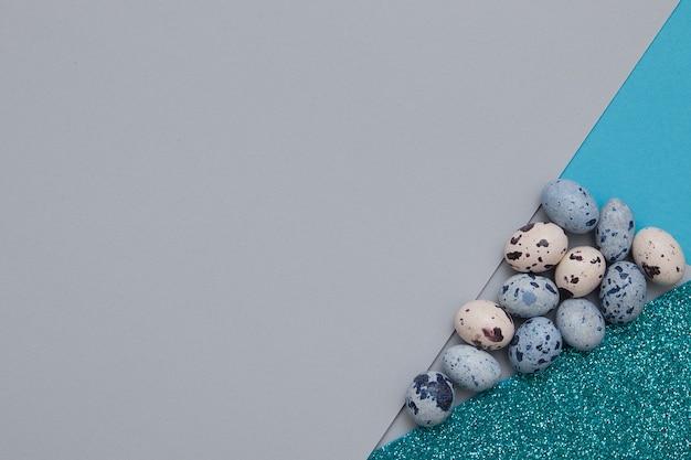 Sfondo creativo di una combinazione di carta, glitter e uova in tonalità blu-verdi per il testo di pasqua