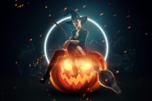 Sfondo creativo la ragazza della strega con la scopa si siede sulla zucca di halloween. bella giovane donna in un cappello da strega.