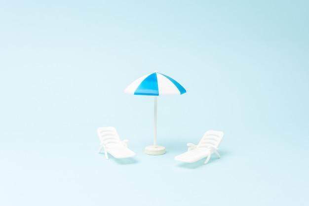 Sfondo creativo con lettini e ombrellone su sfondo blu pastello