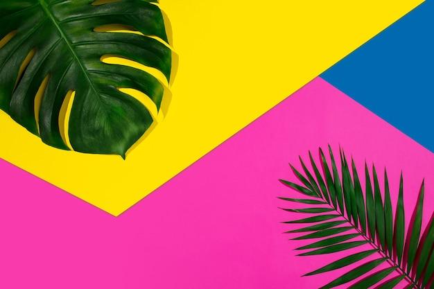 Banner creativo con foglie tropicali su sfondo geometrico di colori vivaci. volantino per annuncio. design per biglietti d'invito, volantini. modelli di design astratti per poster, copertine, sfondi.