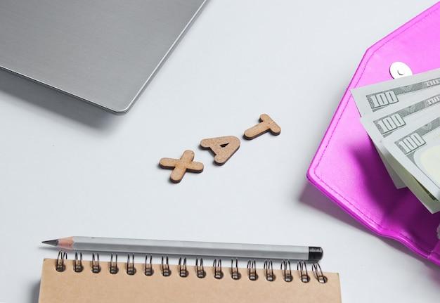 Concetto di business creativo. computer portatile, taccuino, matita, portafoglio con banconote da un dollaro su bianco con la parola tassa di lettere in legno