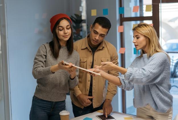 Uomini d'affari creativi che lavorano insieme, discutono di startup, collaborano usando scrum, note adesive