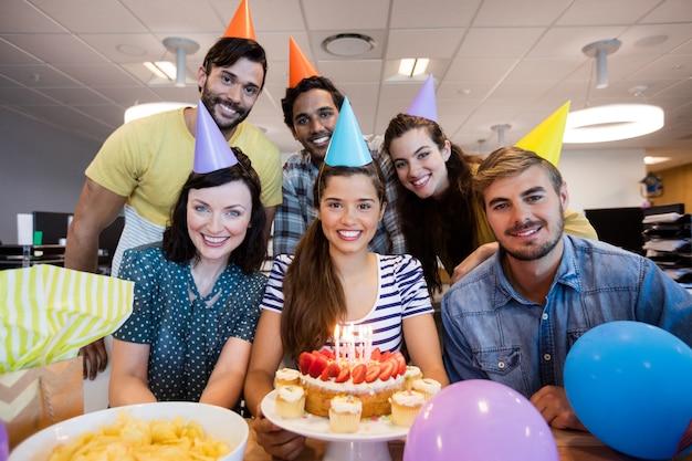 Team aziendale creativo per celebrare il compleanno dei colleghi in ufficio
