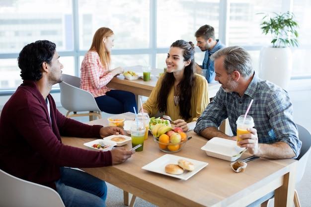 Team aziendale creativo che discute pur avendo un pasto in ufficio
