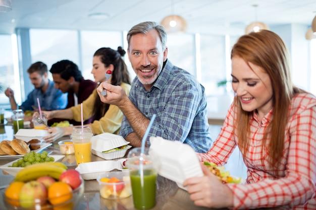 Squadra creativa di affari che mangia all'ufficio