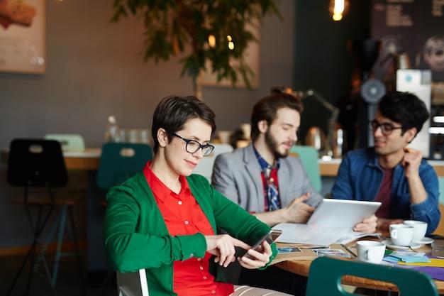 Donna di affari creativa che utilizza smartphone nel caffè