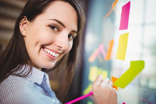 Scrittura creativa della donna di affari sulle note appiccicose attaccate a vetro