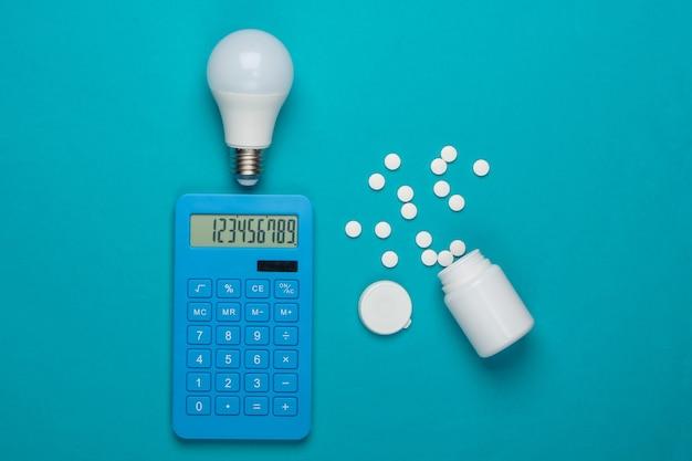 Calcolo creativo del costo delle spese mediche. bottiglia di calcolatrice e pillole, lampadina su sfondo blu. ho un'idea! vista dall'alto. minimalismo