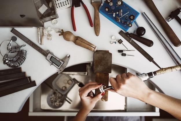 Vista dall'alto del caos creativo del banco da lavoro dei gioiellieri con diversi strumenti per realizzare gioielli femminili