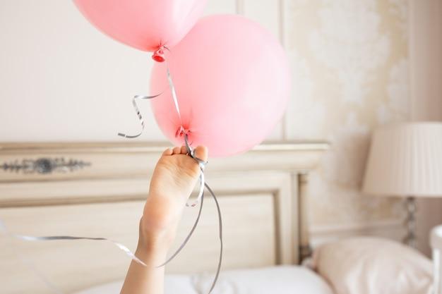 I piccoli piedi creativi del bambino tengono il mazzo di palloncini rosa compleanno interno beige casa in colori chiari