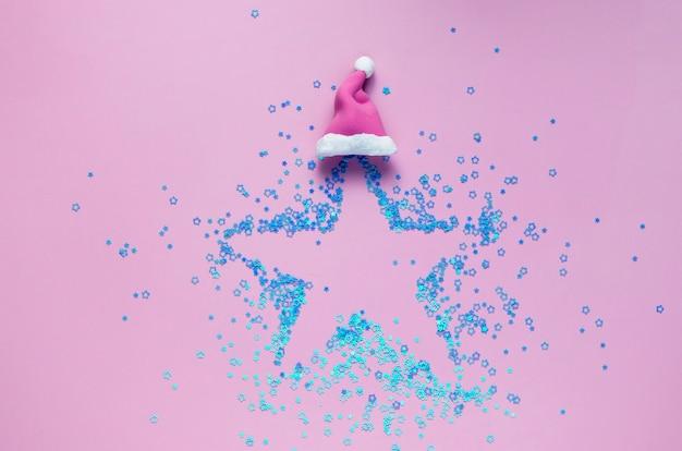 Concetto creativo di natale: forma a stella fatta di mini stelle blu nel cappello di natale