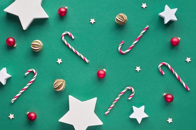 Creativo piatto natalizio con canne di caramella, palline di vetro rosso e frutta secca al lime. scatole regalo di carta a forma di stelle. zero rifiuti natalizi, materiali naturali.