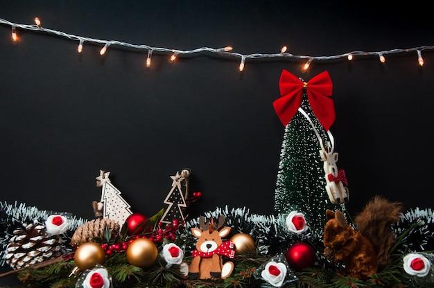 Composizione creativa di natale e capodanno fatta di albero di natale e decorazioni con luce natalizia appesa al muro e cono di pino scoiattolo con albero di abete su vista frontale superficie scura