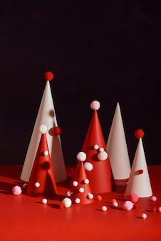 Albero di natale creativo fatto di carta su superficie rossa