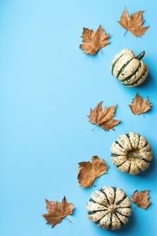Composizione creativa di giorno di autunno di autunno di inverno di natale con le foglie secche decorative. disposizione piana, vista dall'alto, copia spazio, sfondo pastello blu natura morta per biglietto di auguri