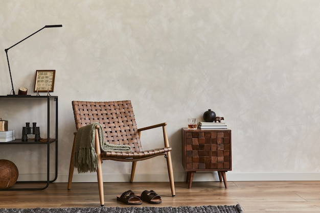 Composizione creativa di eleganti interni maschili soggiorno con spazio copia, poltrona marrone, scaffale industriale, comò progettato e accessori personali. modello.
