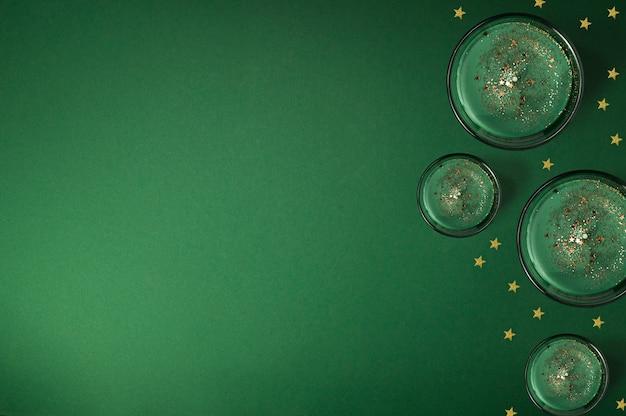 Composizione creativa fatta di candele profumate e stelle dorate lucide su sfondo verde, cornice di natale con spazio di copia, vista piana, vista dall'alto