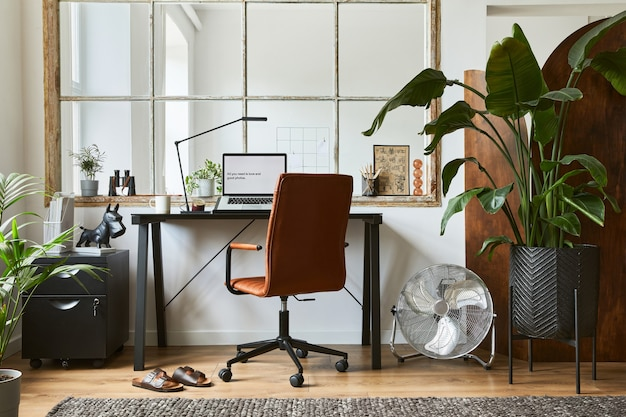 Composizione creativa del moderno design d'interni per l'home office maschile con scrivania industriale nera, poltrona in pelle marrone, laptop e accessori personali eleganti. modello.