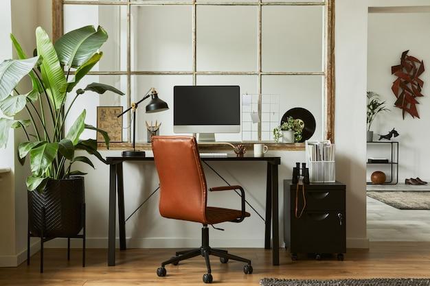 Composizione creativa dell'interno dell'area di lavoro dell'ufficio domestico moderno maschile con scrivania industriale nera, poltrona in pelle marrone, pc e accessori personali eleganti. modello.
