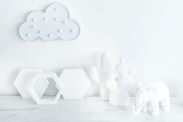 Composizione creativa in stile scandinavo con nuvola sul muro bianco, accessori di forma geometrica e figure bianche di cactus ed elefanti. concetto minimalista bianco. copia spazio. modello.