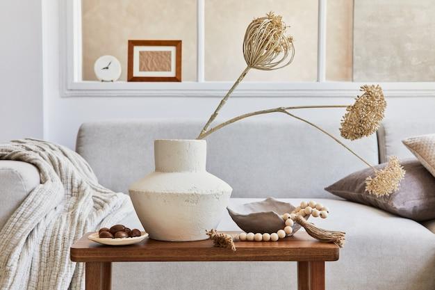 Composizione creativa di interni eleganti e accoglienti del soggiorno con cornice finta, divano grigio, finestra, fiori secchi in vaso e accessori personali. colori neutri beige. particolari. modello.