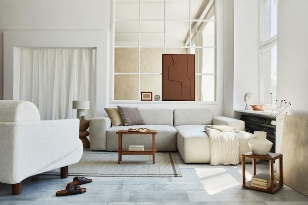 Composizione creativa di interni eleganti e accoglienti del soggiorno con pittura finta della struttura, divano ad angolo grigio, finestra, poltrona e accessori personali. colori neutri beige. modello.
