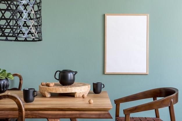 Composizione creativa di interni eleganti della sala da pranzo scandi con finta cornice per poster, tavolo in legno, sedia, pianta e accessori. pareti in eucalipto, pavimento in parquet. modello.