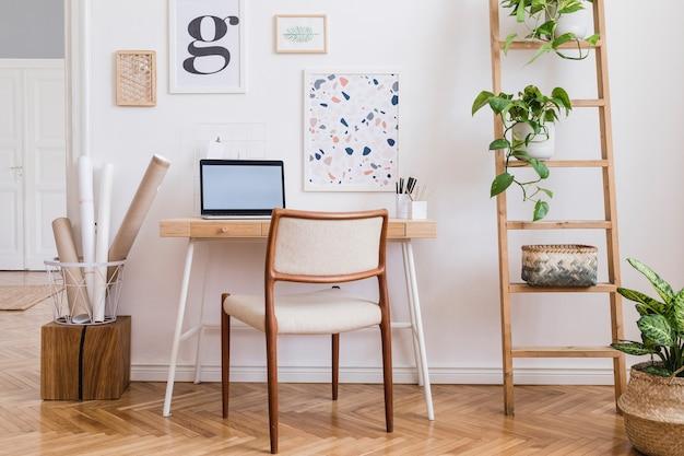 Composizione creativa dell'elegante design d'interni per l'home office scandi con finte cornici per poster, scrivania in legno, sedia, piante e accessori. pareti neutre, pavimento in parquet. modello.