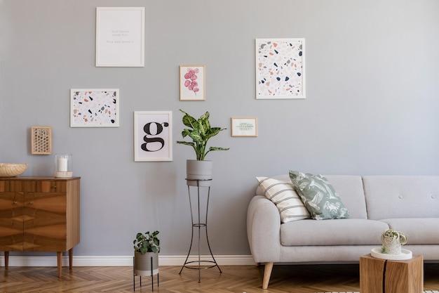 Composizione creativa dell'elegante design degli interni del soggiorno scandi con finte cornici per poster, divano, comò in legno, sedia, piante e accessori. pareti neutre, pavimento in parquet. modello.