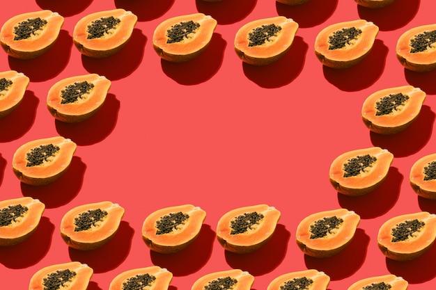 Composizione creativa con frutta fresca di papaia con semi neri su sfondo rosso