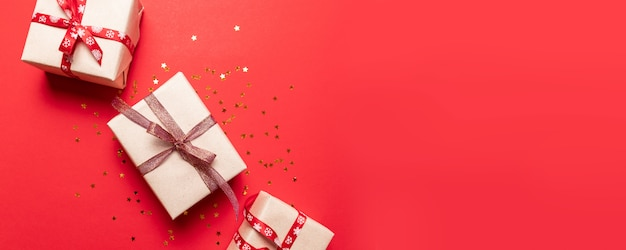 Composizione creativa con scatola regalo rossa, nastri, palline grandi e piccole in oro rosso, decorazioni natalizie su rosso. composizione creativa per compleanno, natale, capodanno