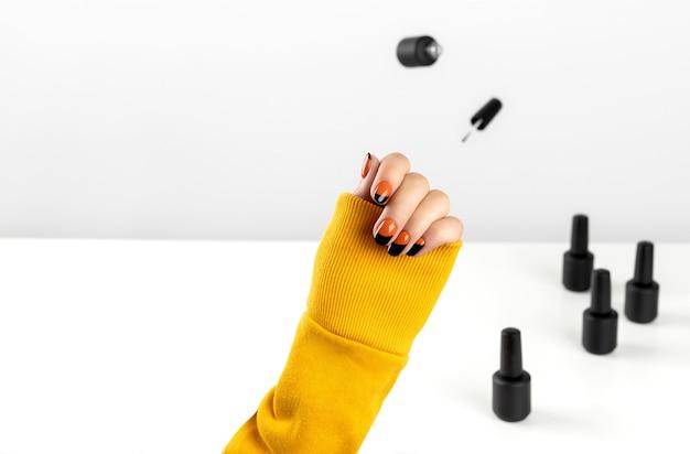 Composizione creativa con le mani della donna e lo smalto per unghie volante