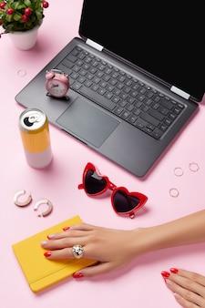 Composizione creativa con gli accessori finali del pianificatore delle mani della donna sul tavolo rosa moda primavera estate femminile