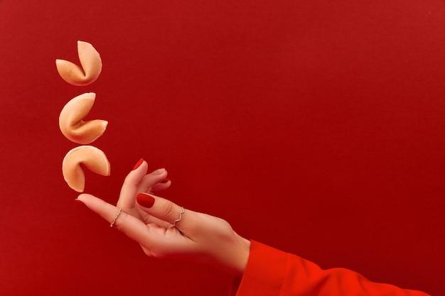 Composizione creativa con la mano delle donne e biscotto della fortuna volante su sfondo rosso
