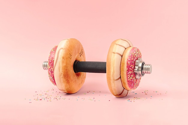 Concept creativo per uno stile di vita sano. manubrio con ciambelle su uno sfondo rosa.