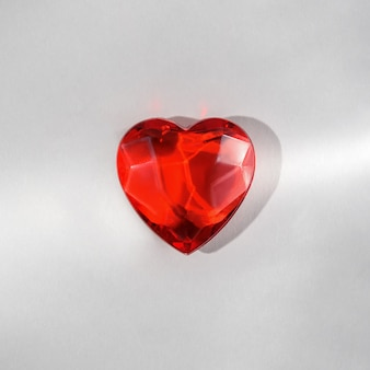 Concetto creativo di amore. cuore di vetro rosso su sfondo grigio.