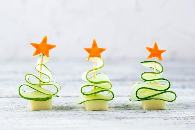 Il concetto creativo imposta alberi di natale di cetriolo, formaggio e stella di carota. cibo per bambini divertenti per la festa di capodanno su sfondo grigio con spazio di copia