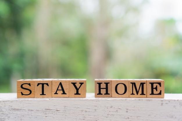 Concetto creativo rimani a casa testo su blocco di legno.