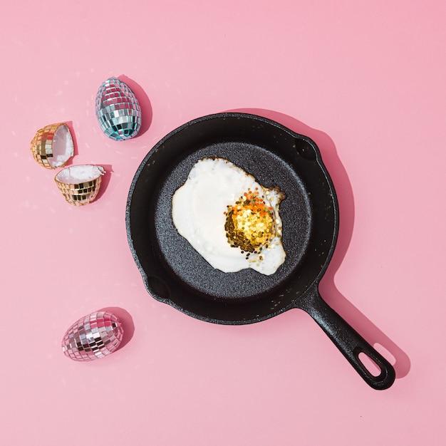 Concetto creativo con uova di palla da discoteca lucide e scintillio dorato sulla superficie rosa pastello