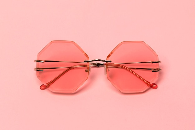 Occhiali da sole alla moda corallo creativi sul tavolo pastello rosa.