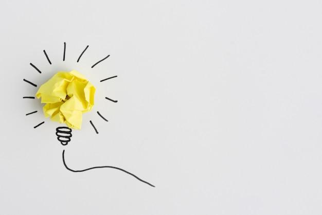 Idea di carta gialla sgualcita creativa della lampadina su fondo bianco