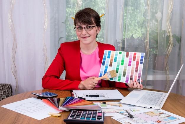 Designer creativo con matite nei capelli che mostrano la tavolozza dei colori