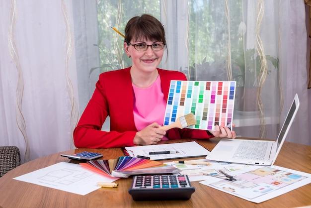 Designer creativo con matite nei capelli che mostra la tavolozza dei colori