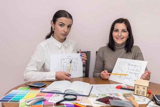 Designer creativi che mostrano il piano della casa e in posa per la fotocamera