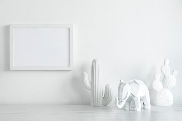 Scrivania creativa in stile scandinavo con cornice bianca finta e figura bianca di cactus ed elefante