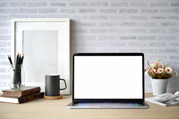Area di lavoro di scrivania creativa con poster cornice vuota, laptop schermo vuoto