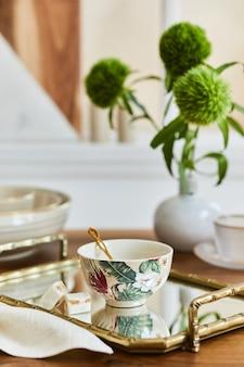 Composizione per sala da pranzo creativa ed elegante con porcellane di classe, vassoio dorato e bellissimi accessori personali. appartamenti di lusso. bellezza nei dettagli. modello.